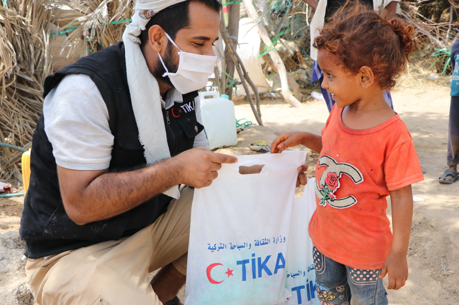 A TIKA worker hands an aid package to a girl in Yemen, May 21, 2020. (AA Photo)
