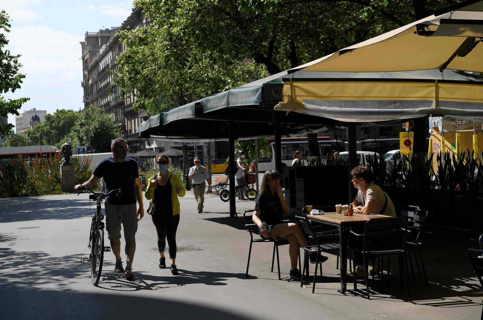 People sit at a terrace bar in Las Ramblas, Barcelona, May 25, 2020. (AFP Photo)