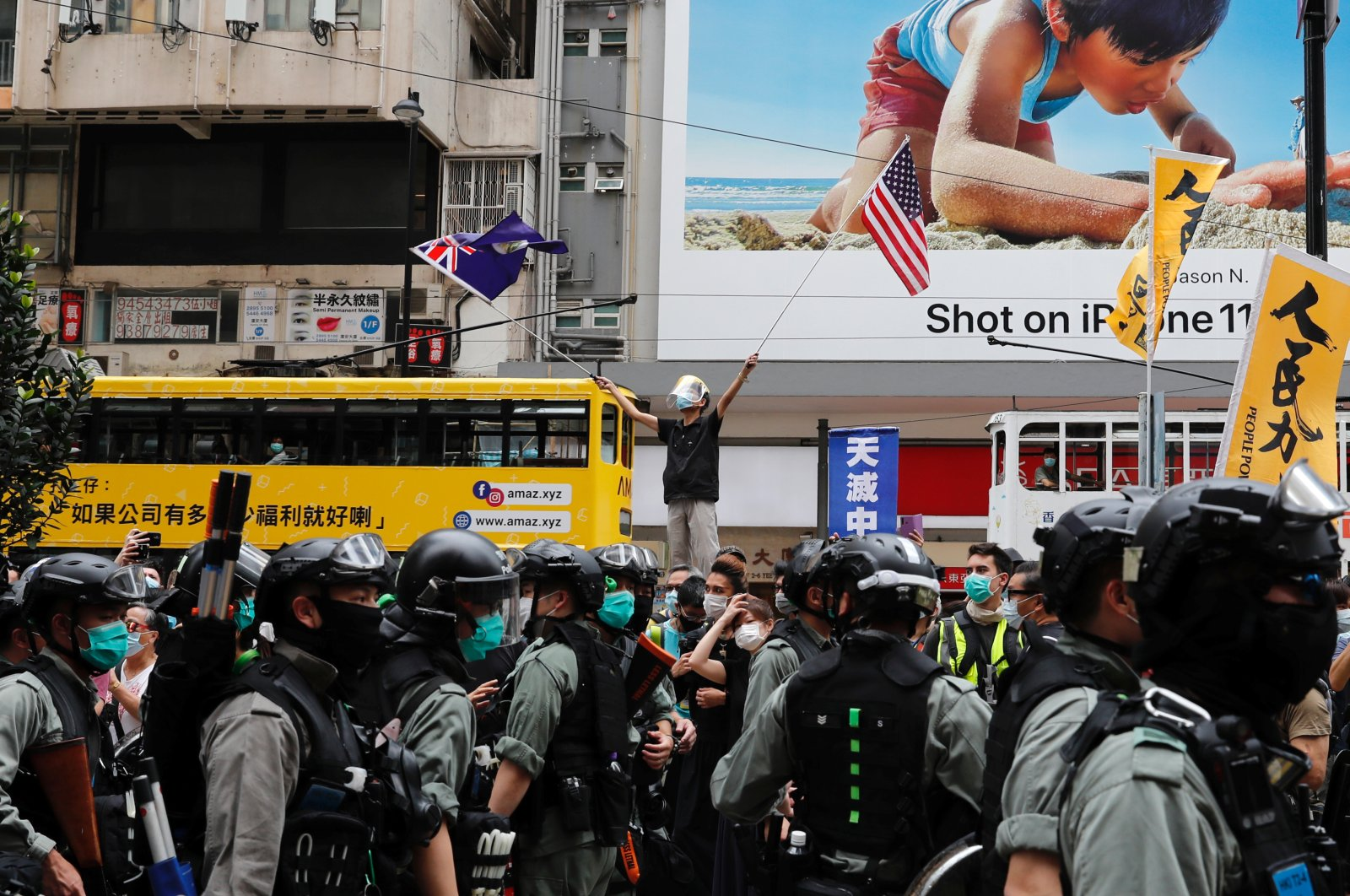 An anti-government protester waves the U.S. and the British colonial Hong Kong flags as riot police walk past during a march against Beijing's plans to impose national security legislation in Hong Kong, May 24, 2020. (Reuters Photo)
