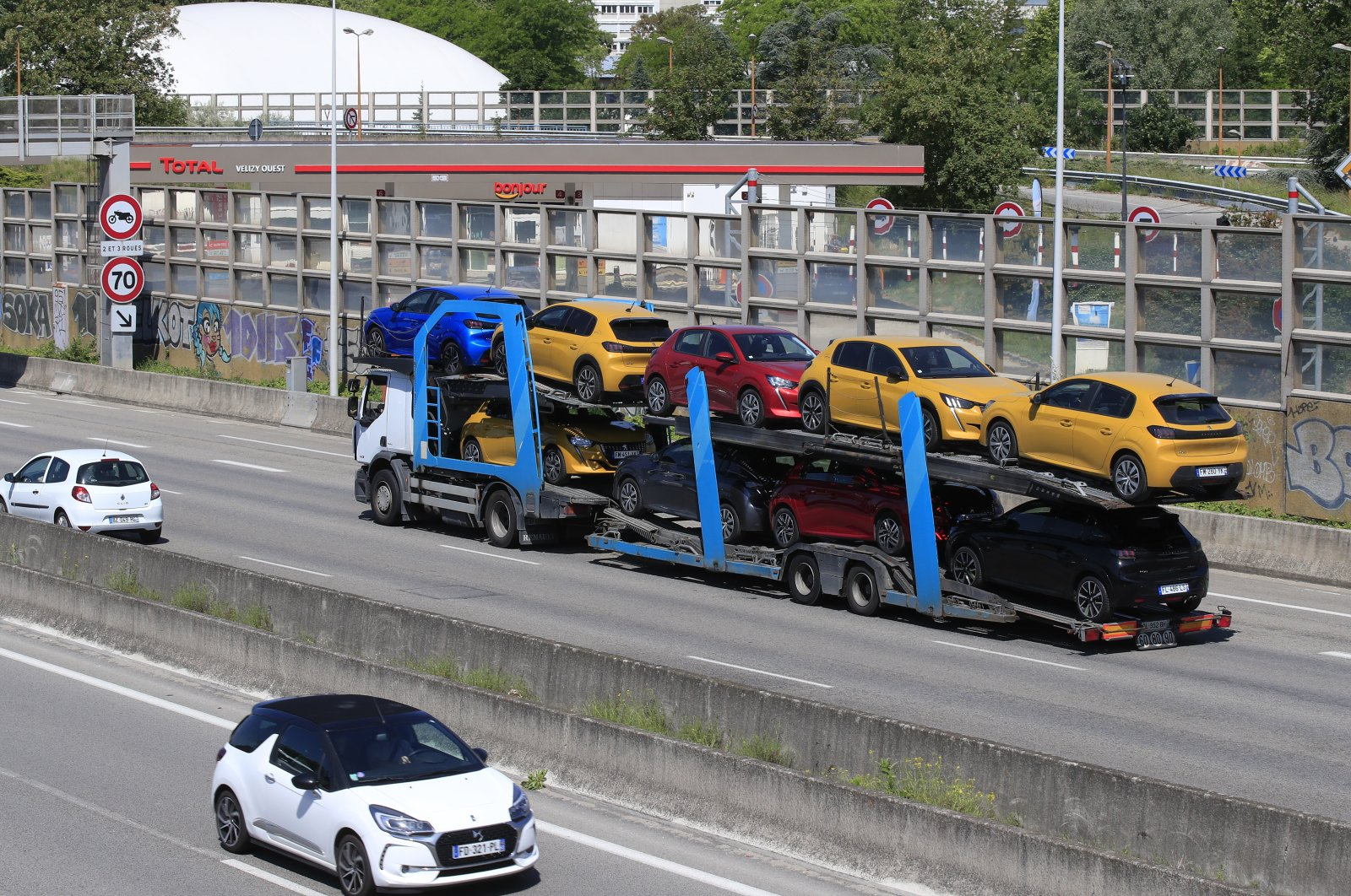 A truck carries new cars on the motorway leading to Paris, May 26, 2020 in Villacoublay, west of Paris. (AP Photo)