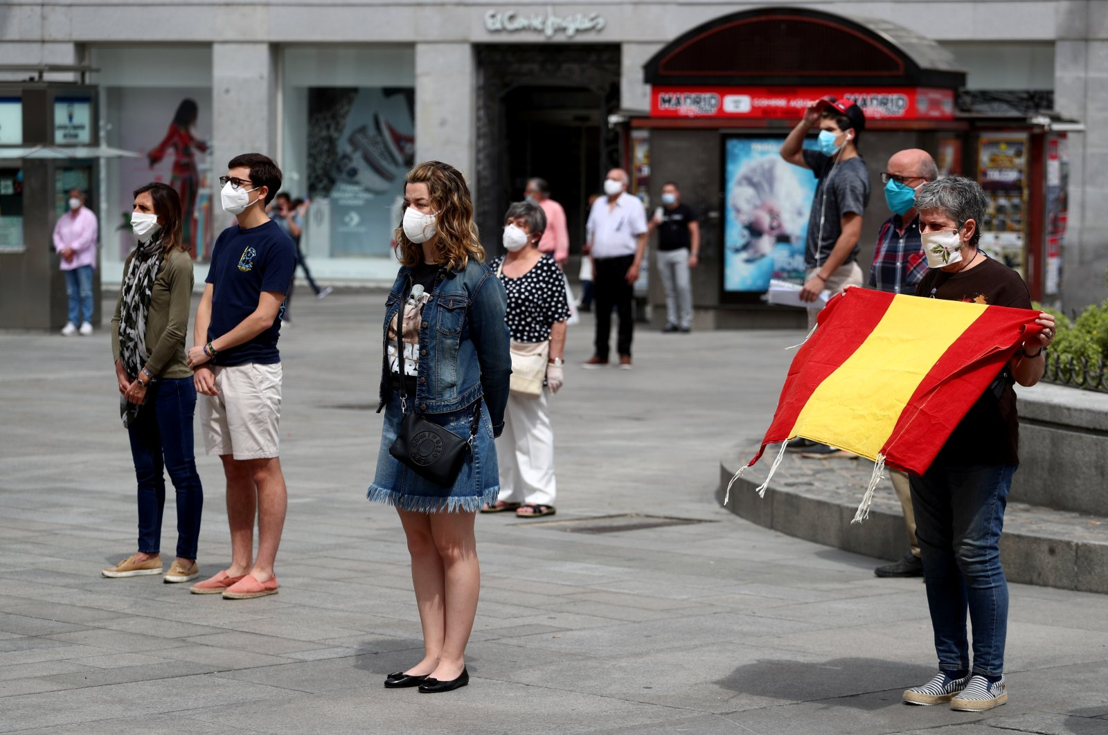 People wearing protective face masks stand during a daily minute of silence to commemorate victims of the coronavirus disease (COVID-19), at Puerta del Sol square in Madrid, Spain, May 26, 2020. (Reuters Photo)