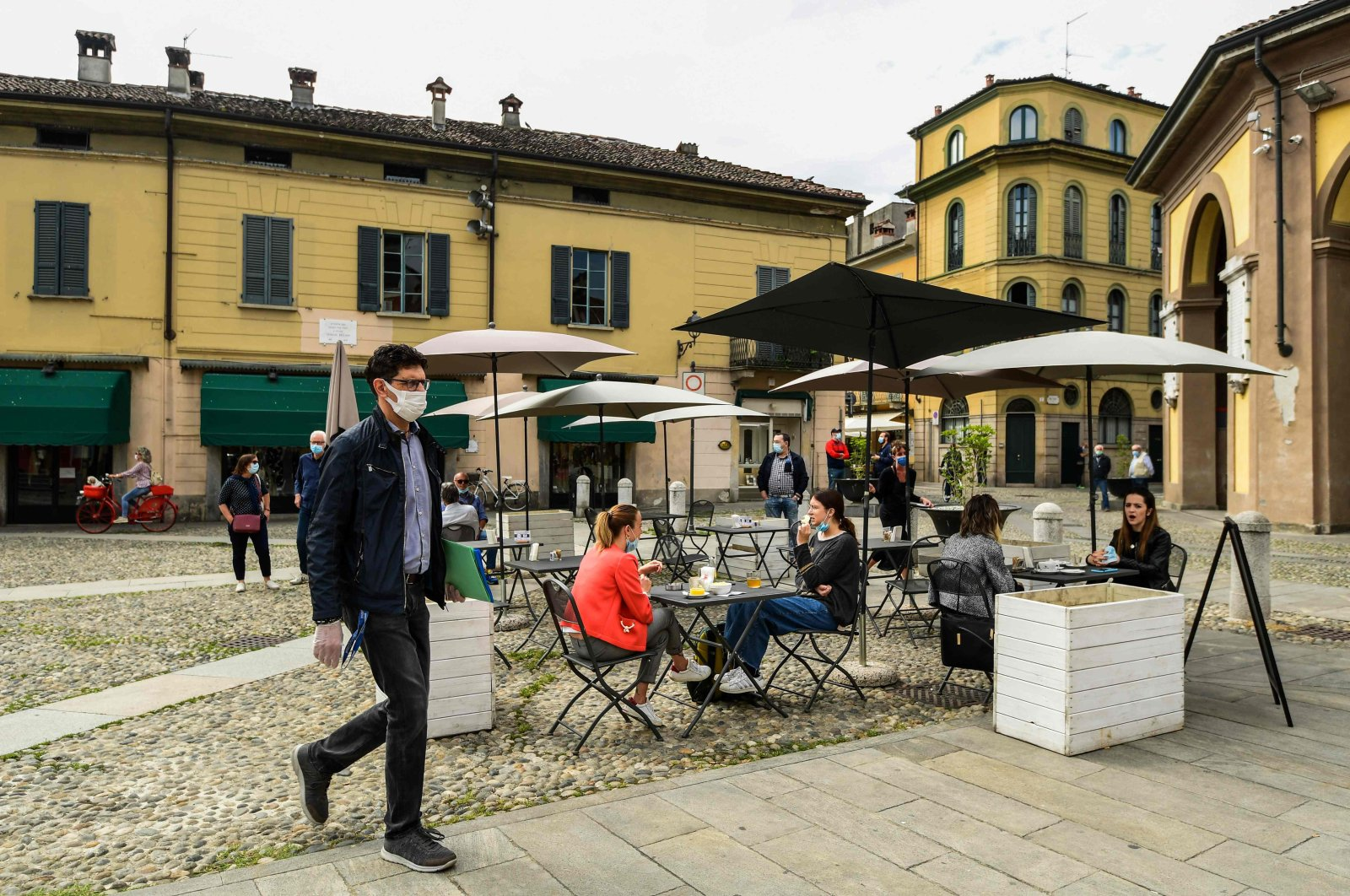 Residents have a drink at a cafe terrace and go about their activities in central Codogno, southeast of Milan, one of the villages at the epicenter of the coronavirus pandemic, Italy, May 20, 2020. (AFP Photo)