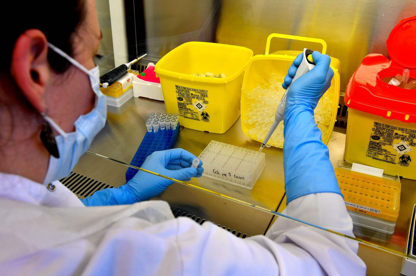 A lab assistant manipulates samples, at a COVID-19 screening centre of Saint Andre Hospital in Bordeaux, France on May 20, 2020. (AFP Photo)