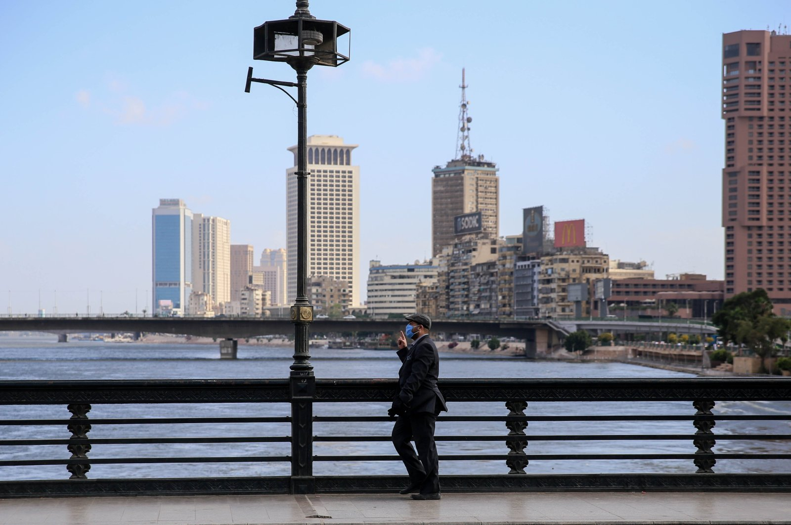A mask-clad man walks along the Kasr el-Nil bridge connecting the island district of Zamalek to the city center of Cairo, May 24, 2020. (AFP Photo)