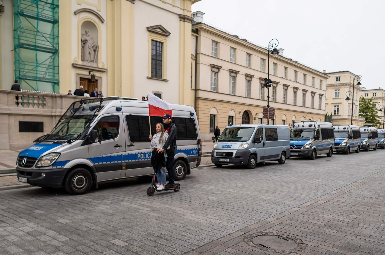 A couple riding an electric scooter and holding a Polish flag passes a column of police vehicles after a demonstration of Polish entrepreneurs and business owners against right-wing government and coronavirus restrictions in the center of Warsaw, Poland on May 23, 2020. (AFP Photo)