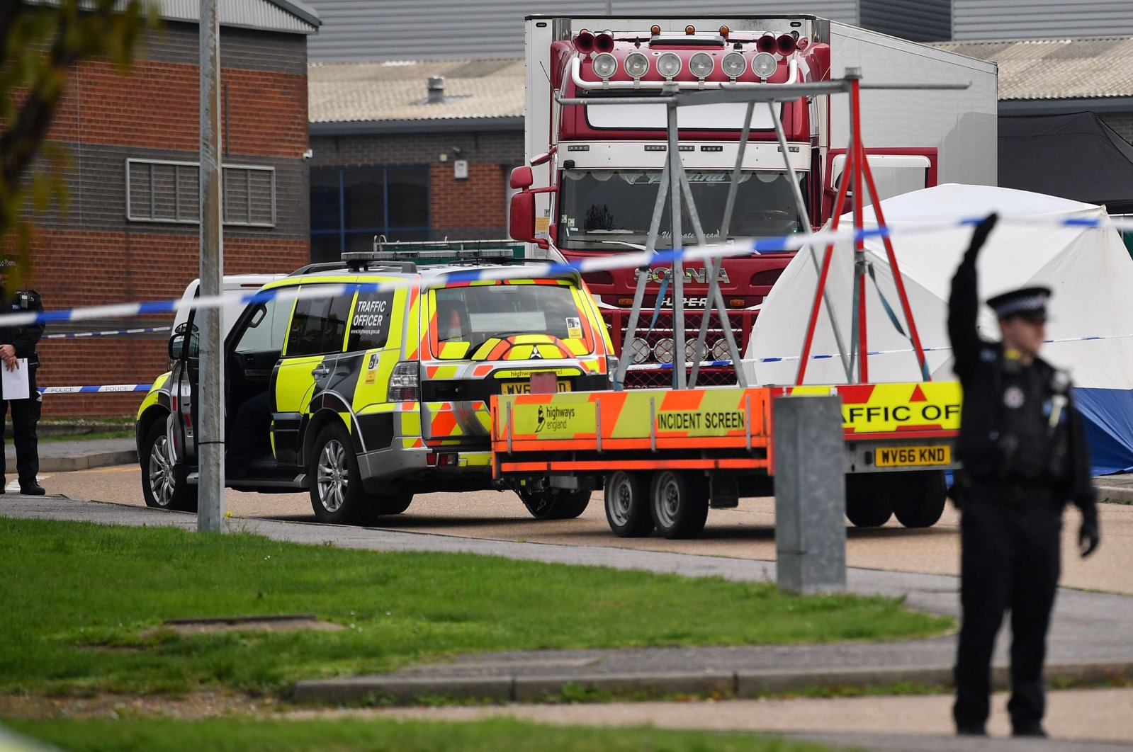 British Police officers work by a lorry, believed to have originated from Bulgaria, and containing 39 dead bodies, discovered at Waterglade Industrial Park in Grays, east of London, Oct. 23, 2019. (AFP Photo)