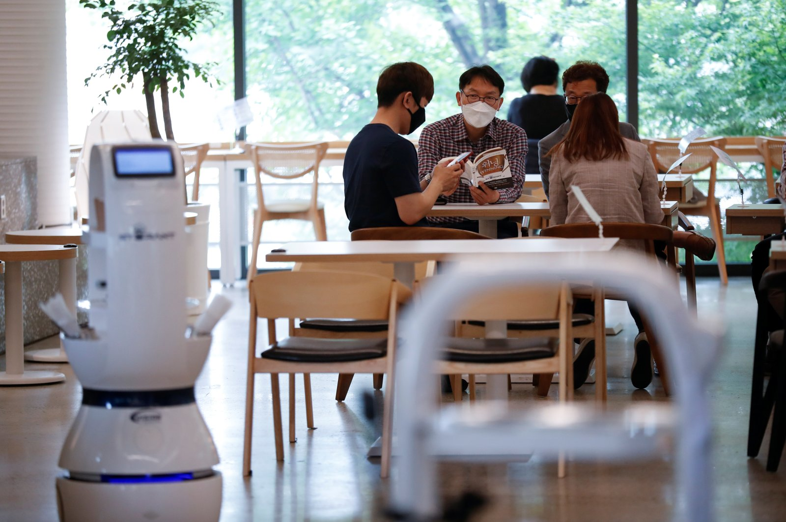 Customers wait at a cafe where a robot that takes orders, makes coffee and brings the drinks straight to customers is being used in Daejeon, South Korea, May 25, 2020. (Reuters Photo)