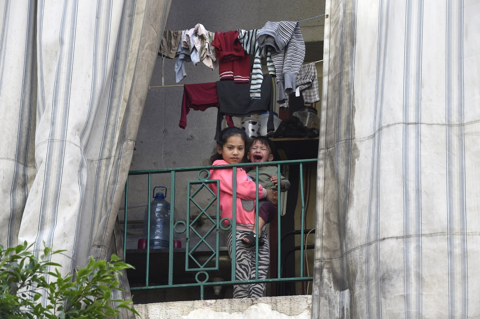 A Syrian refugee girl holds her crying younger brother as she looks on from a balcony in a residential building where Syrian refugees who have tested positive for the novel coronavirus remain quarantined in Beirut, Lebanon, May 20, 2020. (EPA Photo)
