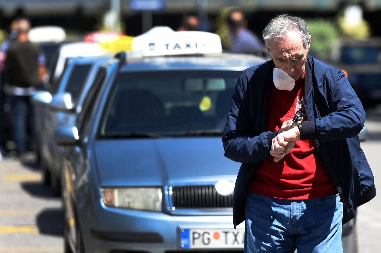 A man wearing a face mask walks past a taxi station in Podgorica, Montenegro, May 4, 2020. (EPA)
