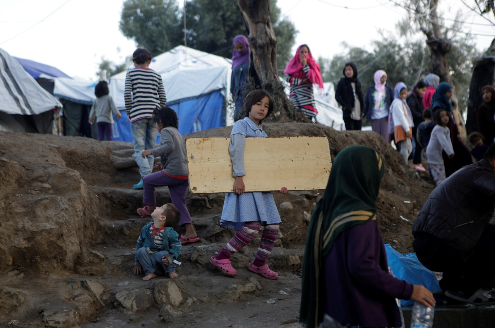 A girl carries a wooden board as she makes her way at a makeshift camp for refugees and migrants next to the Moria camp, on the island of Lesbos, Greece, Nov. 15, 2019. (REUTERS)