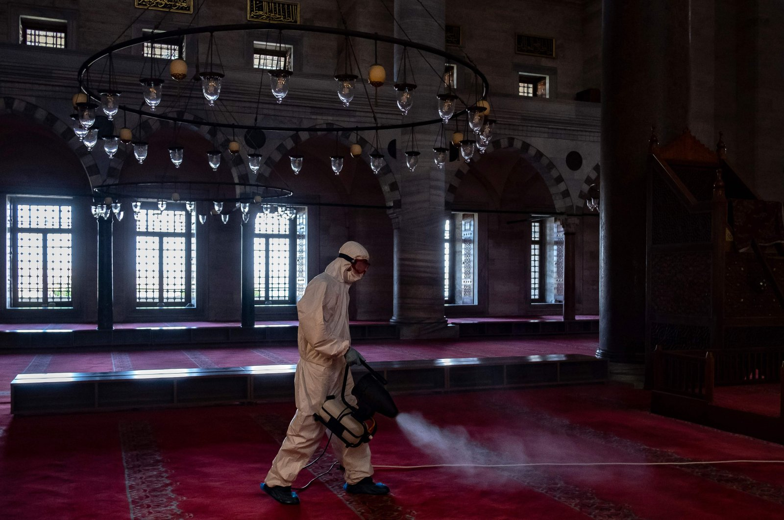 A Fatih Municipality worker disinfects the Suleymaniye Mosque before its reopening on the last day of the Eid al-Fitr in Istanbul, on May 26, 2020 amid the spread of the COVID-19 pandemic, caused by the novel coronavirus. (AFP Photo)