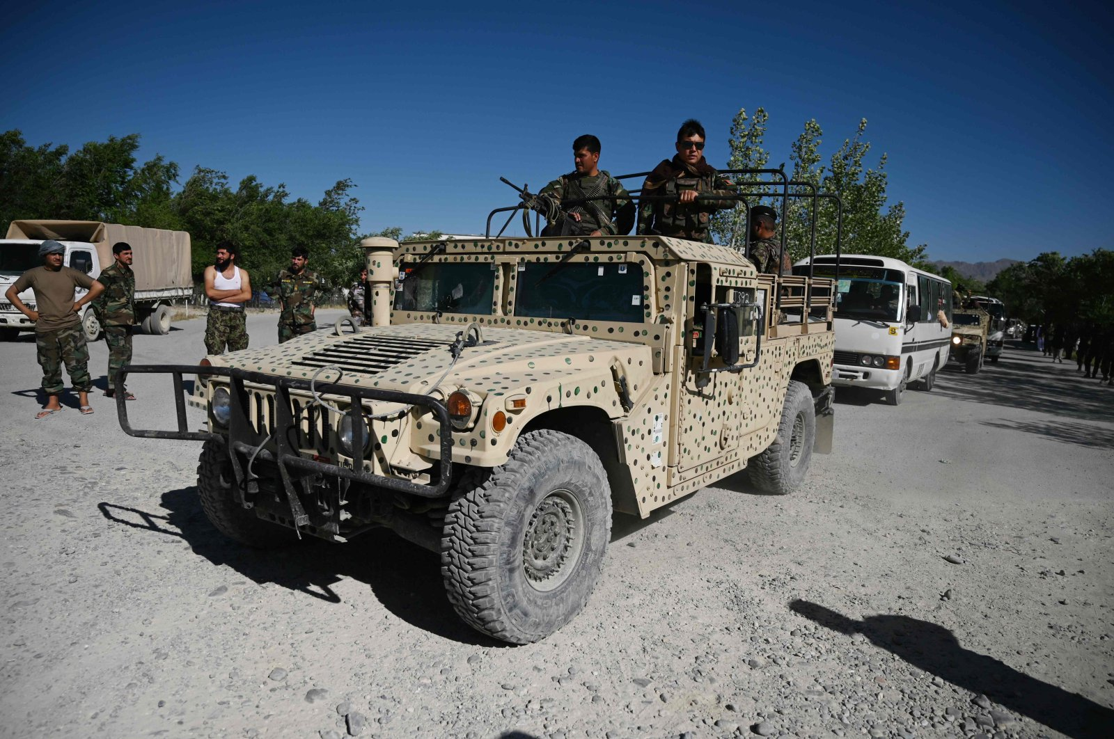 Afghan National Army (ANA) soldier escorts Taliban prisoners convoy during their release from the Bagram prison, in outside of the US military base in Bagram, some 50 km north of Kabul on May 26, 2020. (AFP Photo)