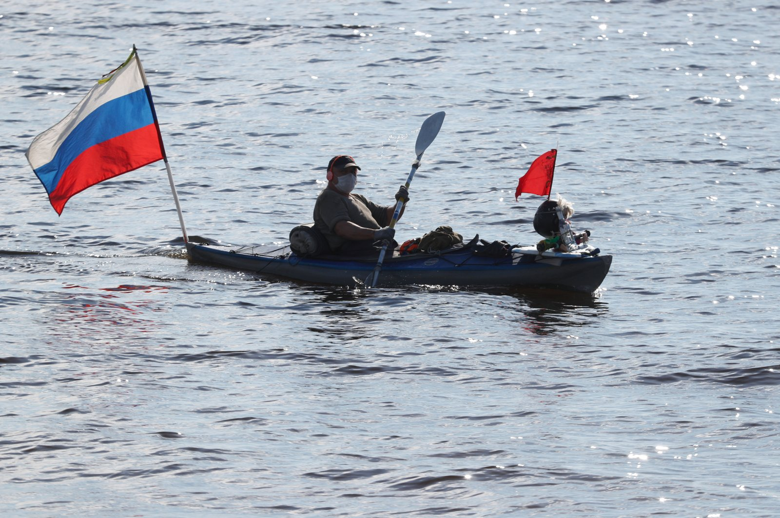 A man wearing a protective face mask paddles a canoe in the waters of the Gulf of Finland amid the outbreak of the coronavirus disease in St. Petersburg, Russia May 27, 2020. (Reuters Photo)