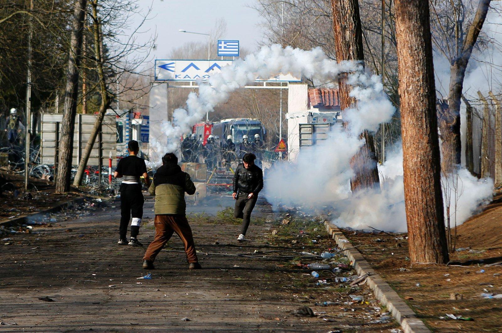 A migrant runs away from tear gas at Turkey's Pazarkule border crossing with Greece's Kastanies, near Edirne, Turkey, March 2, 2020. (REUTERS)