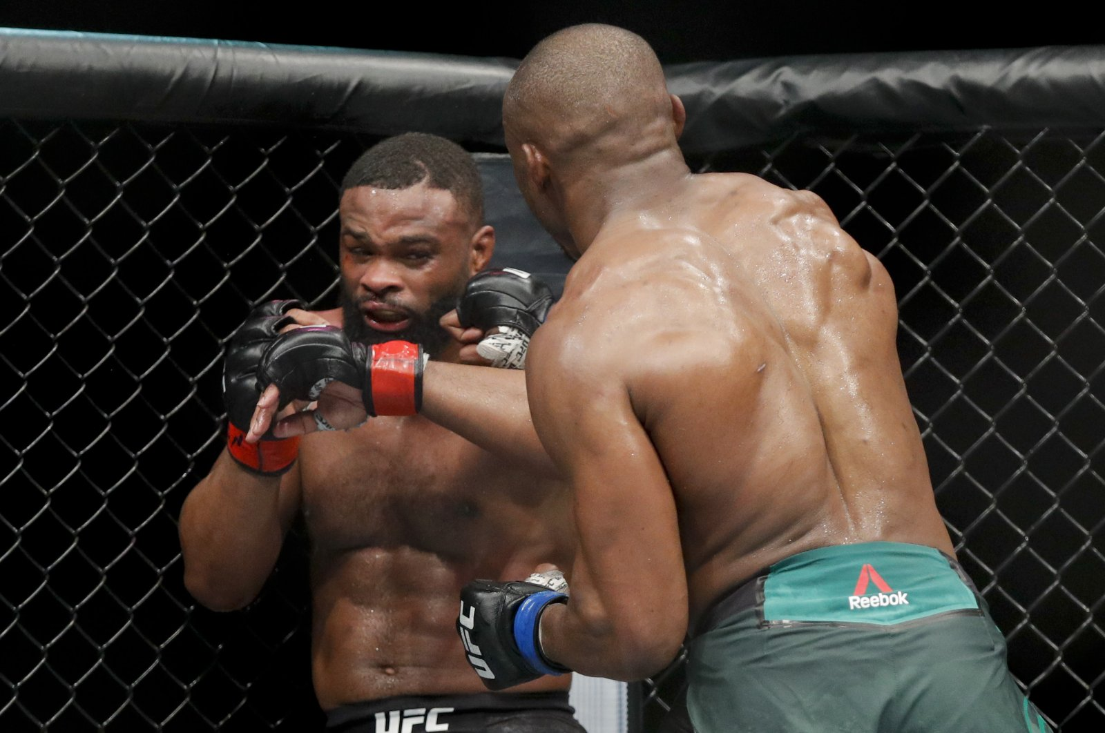 Kamaru Usman (R) hits Tyron Woodley in a welterweight mixed martial arts title fight at UFC 235, Las Vegas, U.S., March 2, 2019. (AP Photo)