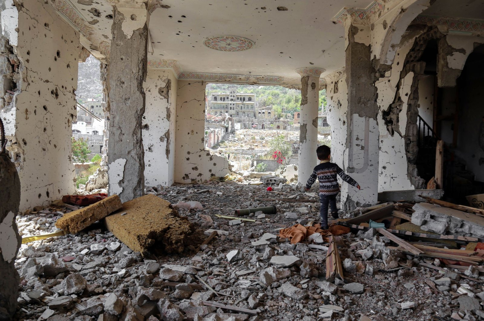 A Yemeni child walks in the rubble of a building that was destroyed in an airstrike in Taez, southern Yemen, March 18, 2018. (AFP Photo)