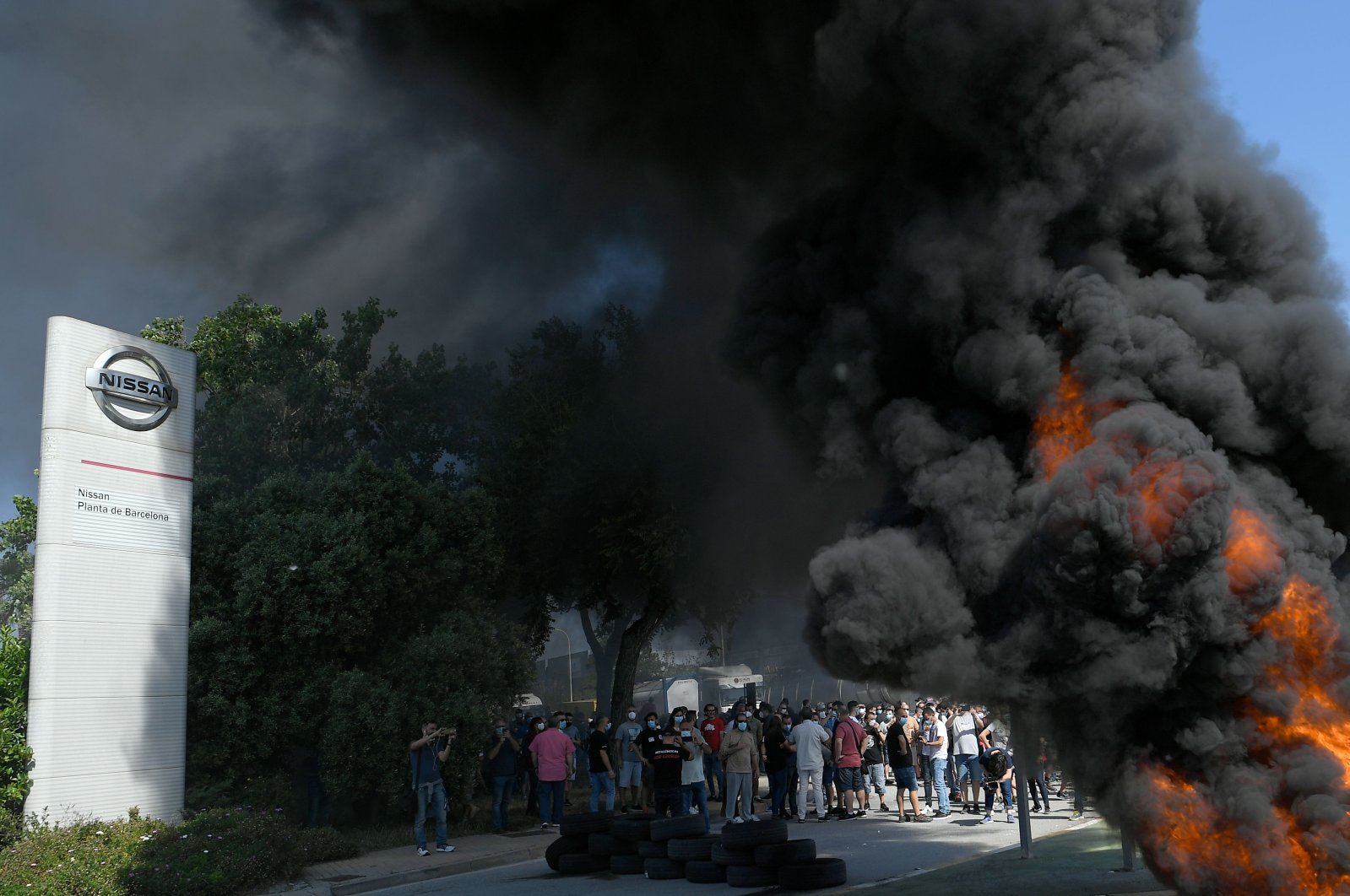 Nissan employees burn tires in front of the Japanese car manufacturer's plant in Barcelona on May 28, 2020. (AFP Photo)
