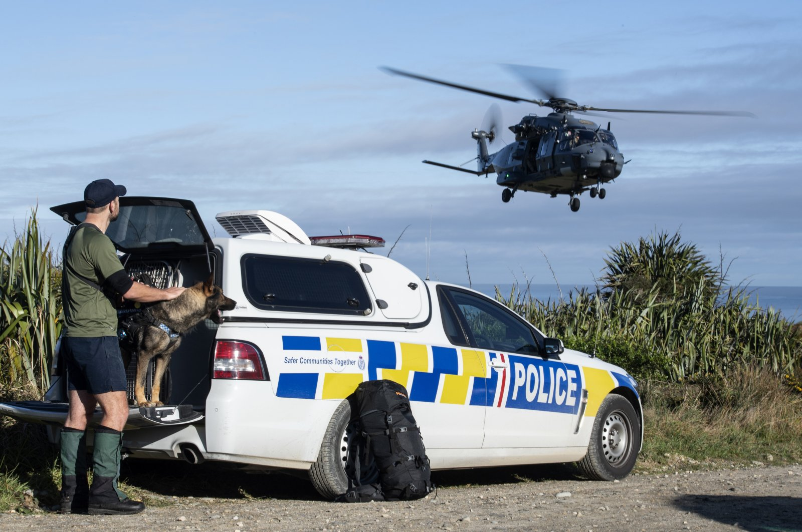 In this photo provided by the New Zealand Defence Force, a police officer watches as a helicopter takes off during a rescue operation to find two missing trampers in the Kahurangi National Park in the South Island of New Zealand, Wednesday, May 27, 2020. (CPL Naomi James/New Zealand Defence Force via AP)