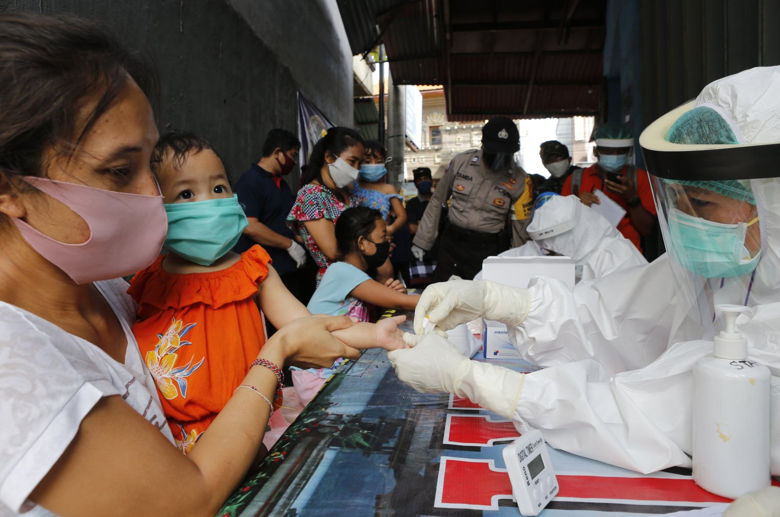 A mother holds her daughter to receive a coronavirus antibody test from health workers at a village in Bali, Indonesia, May 27, 2020. (AP Photo)