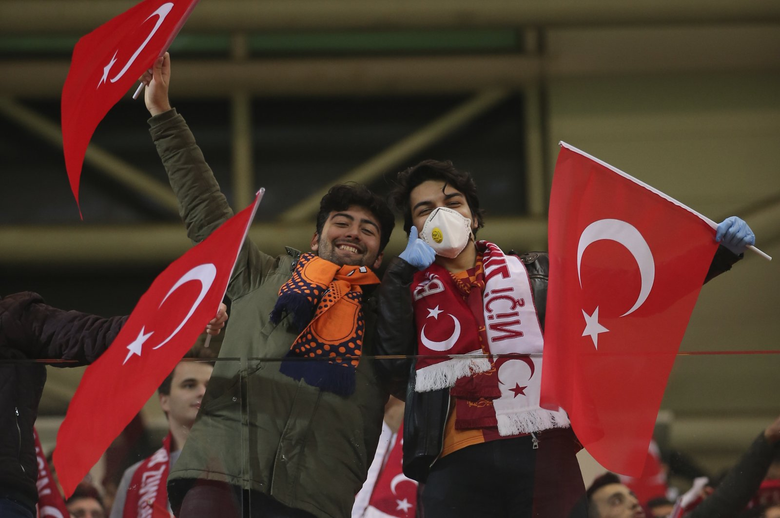 Spectators, some wearing masks because of the coronavirus outbreak, wave Turkish flags prior to a Europa League top 16 first leg football match between Başakşehir and Copenhagen, in Istanbul, Turkey, March 12, 2020. (AP Photo)