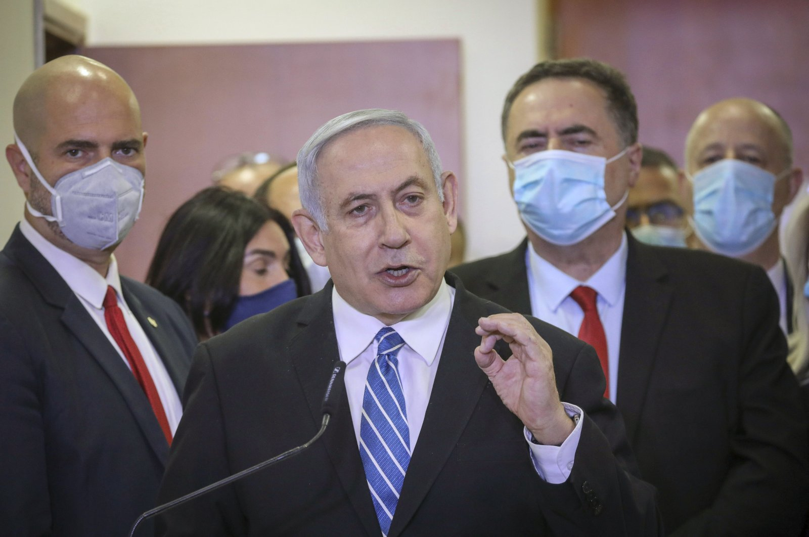Israeli Prime Minister Benjamin Netanyahu accompanied by members of his Likud Party in masks delivers a statement before entering the district courthouse, Jerusalem, May 24, 2020. (AP Photo)