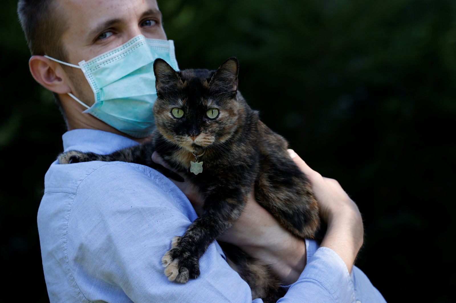 Brian, 24-year-old, suspected to have been infected by COVID-19 poses in his garden with Papille, his nine-year-old cat who recovered after being tested positive for the virus in Athis-Mons, near Paris, France, May 27, 2020. REUTERS/Christian Hartmann