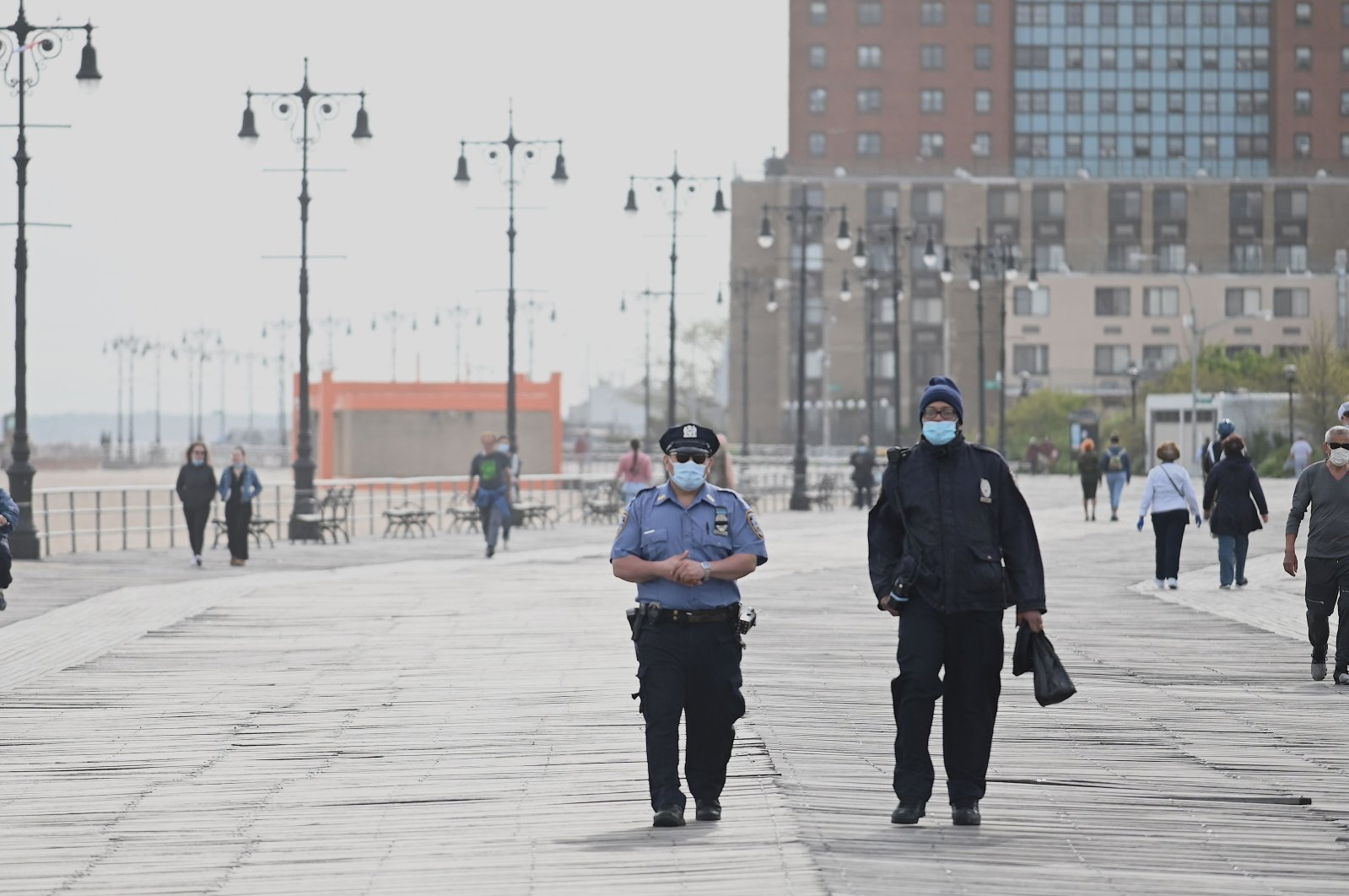 Policemen wearing masks patrol at the promenade at Coney Island Beach on May 18, 2020 in New York City. (AFP Photo)