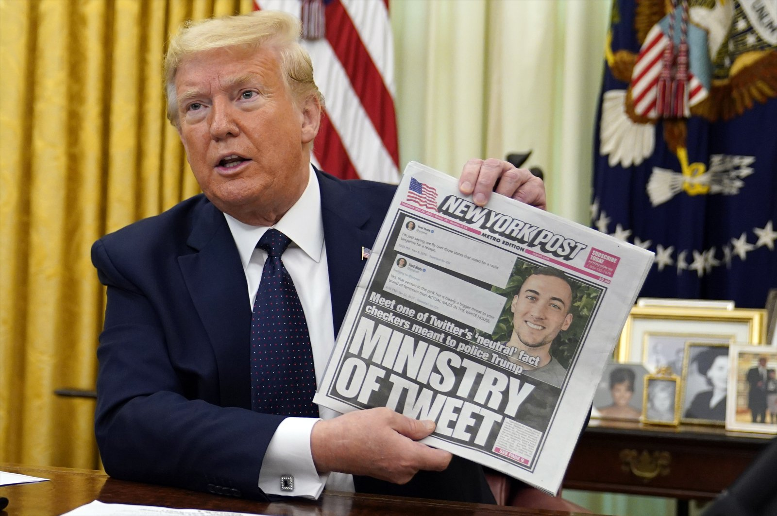 President Donald Trump holds up a copy of the New York Post as speaks before signing an executive order aimed at curbing protections for social media giants, in the Oval Office of the White House, Thursday, May 28, 2020, in Washington. (AP Photo)