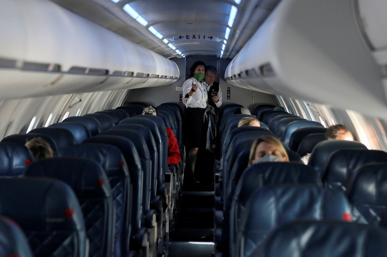 Flight attendants talk in a nearly empty cabin on a Delta Airlines flight operated by SkyWest Airlines as travel has cutback, amid concerns of the coronavirus during a flight departing from Salt Lake City, Utah, U.S., April 11, 2020. (REUTERS Photo)