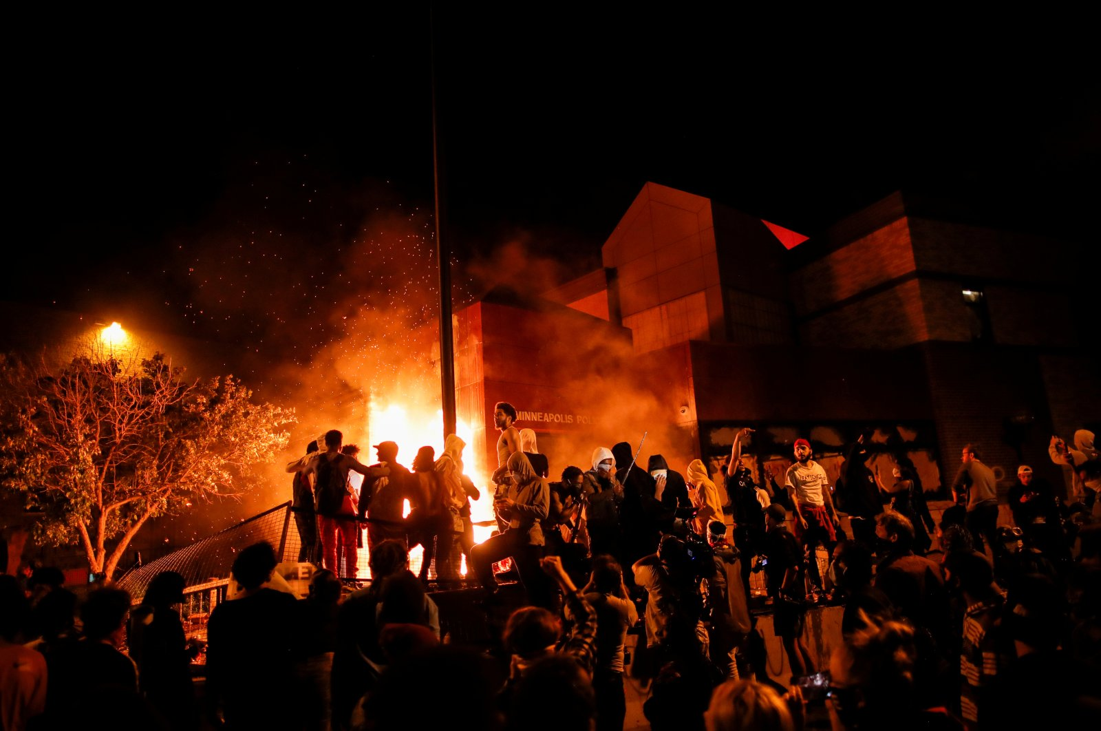 Protesters gather around after setting fire to the entrance of a police station as demonstrations continue after a white police officer was caught on a bystander's video pressing his knee into the neck of African-American man George Floyd, who later died at a hospital, in Minneapolis, Minn., May 28, 2020. (Reuters Photo)
