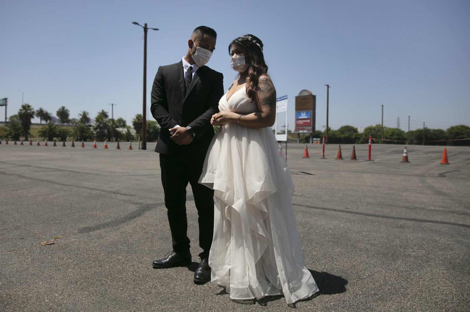 Roselle Querido, right, and her bridegroom Mo de las Alas wait for their marriage service to begin in the parking lot of the Honda Center in Anaheim, Calif., Tuesday, May 26, 2020. (AP Photo)