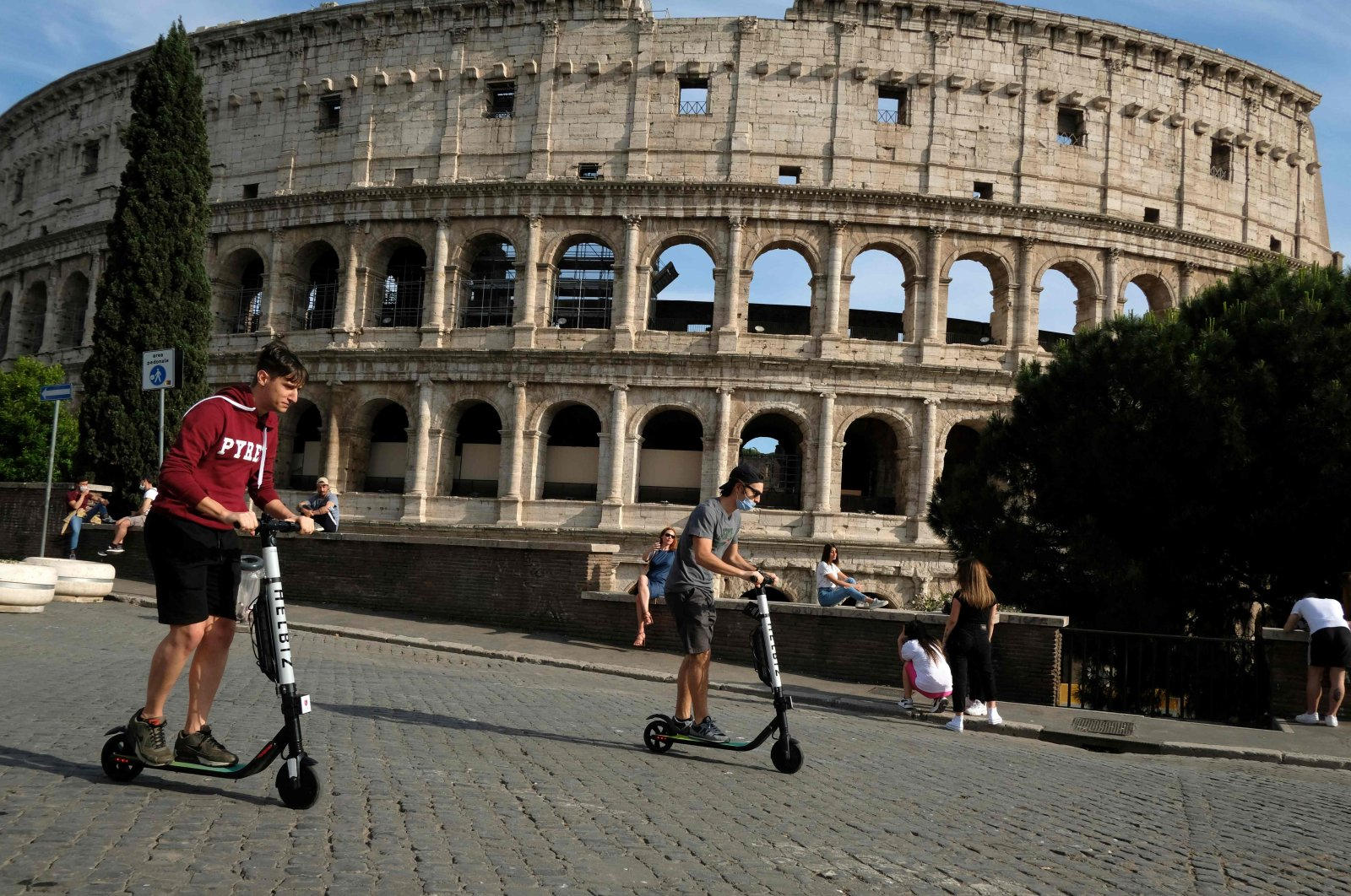 People ride electric scooters, past the Colosseum monument, Rome, May 28, 2020. (AFP Photo)