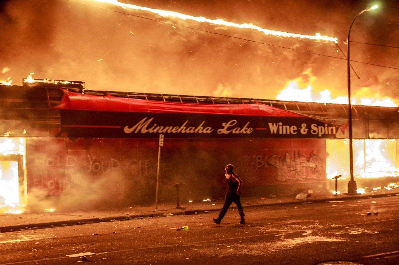 A man walks past a liquor store in flames near the Third Police Precinct during a protest over the death of George Floyd, an unarmed black man, who died after a police officer kneeled on his neck for several minutes, Minneapolis, Minnesota, May 28, 2020. (AFP Photo)