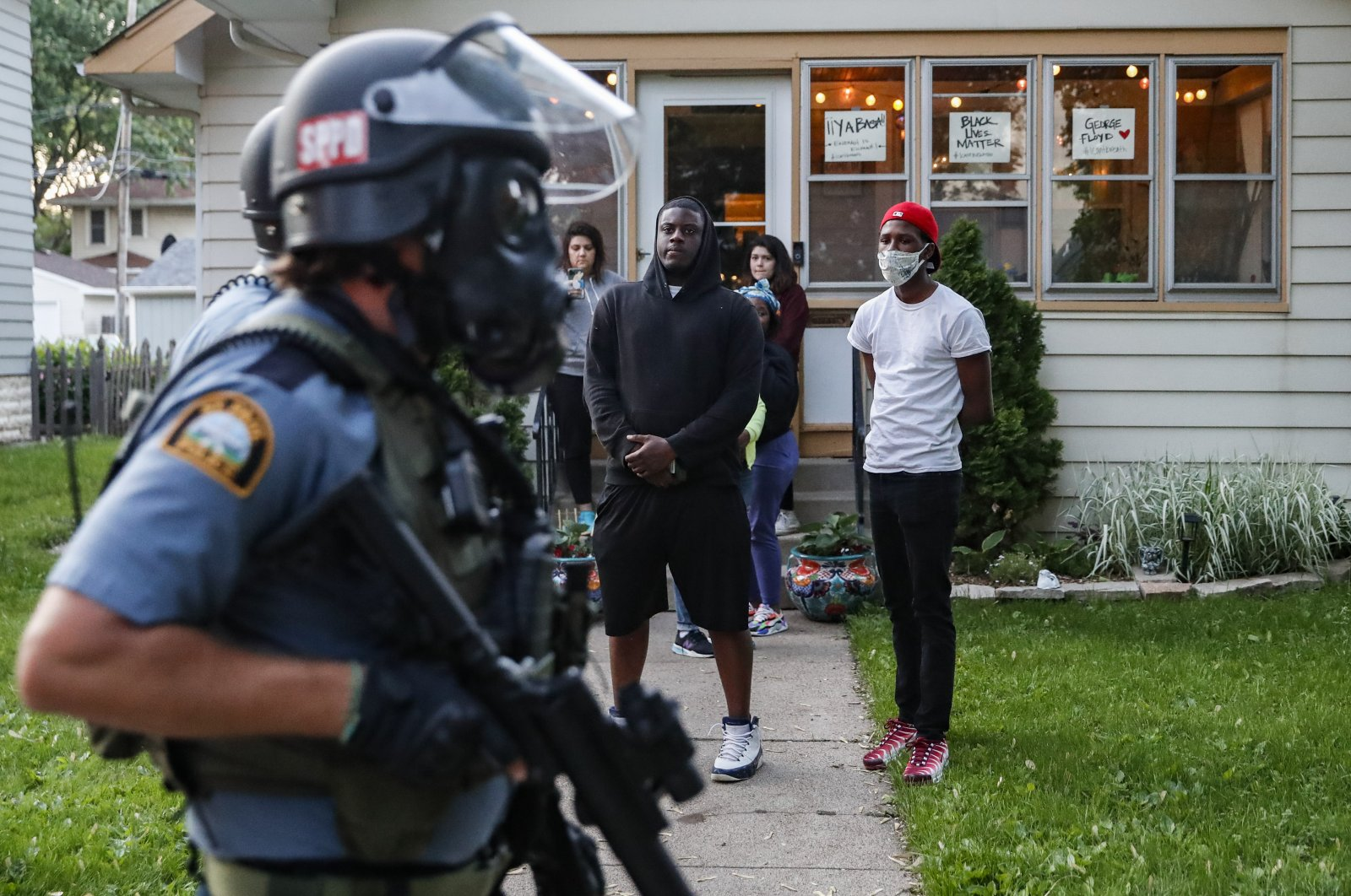 Protestors watch as police in riot gear walk down a residential street, Thursday, May 28, 2020, in St. Paul, Minn. (AP Photo)