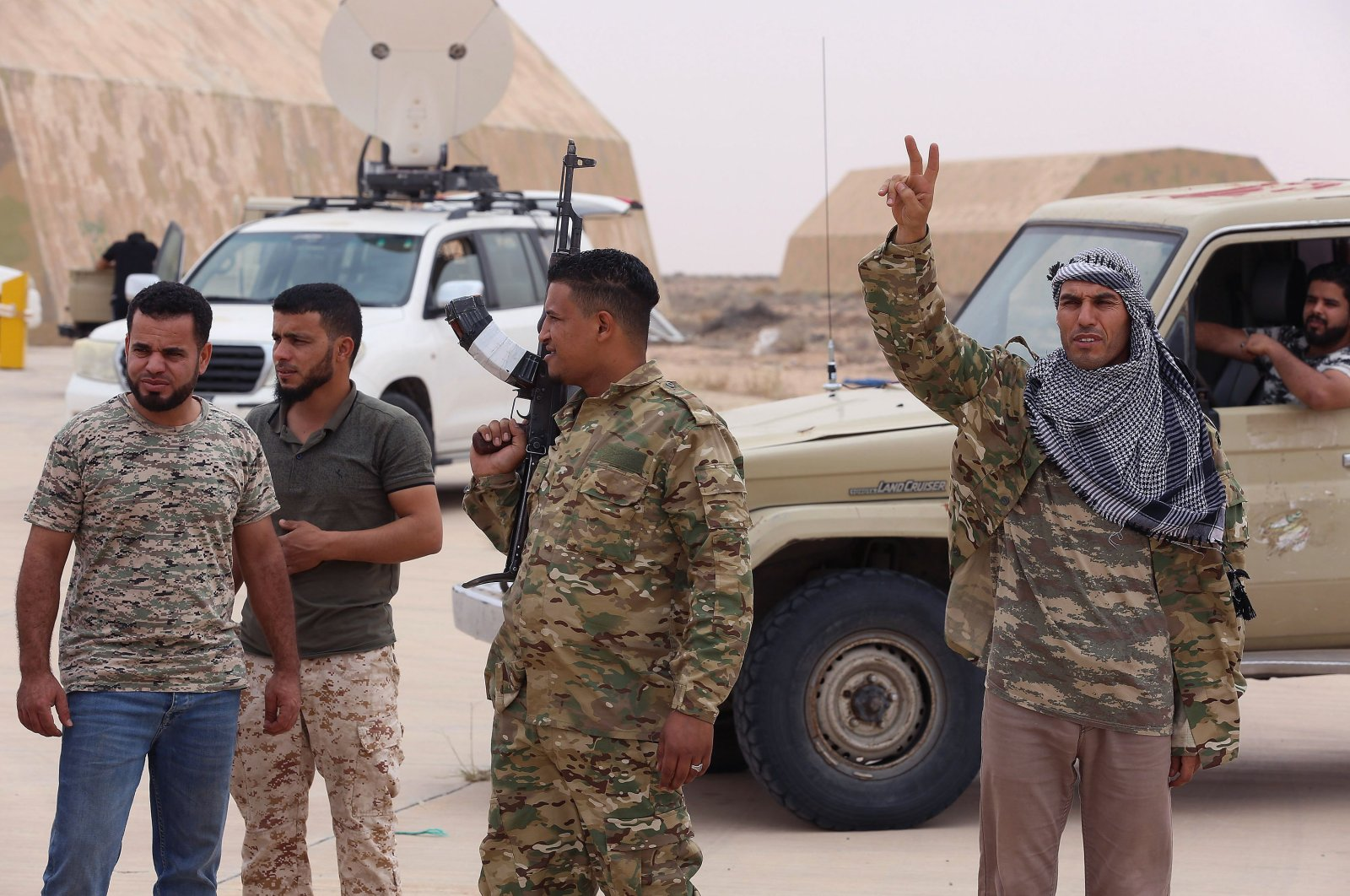 Fighters loyal to Libya's UN-recognised Government of National Accord (GNA) stand outside a hangar at Al-Watiya airbase, which they seized control of, southwest of the capital Tripoli, May 18, 2020. (AFP)