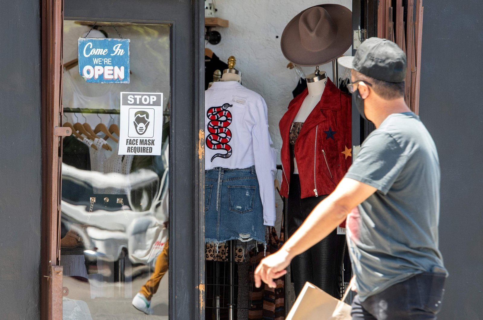 A man wearing a mask walks by a store requiring shoppers wear masks during the coronavirus pandemic, Los Angeles, California, May 27, 2020. (AFP Photo)