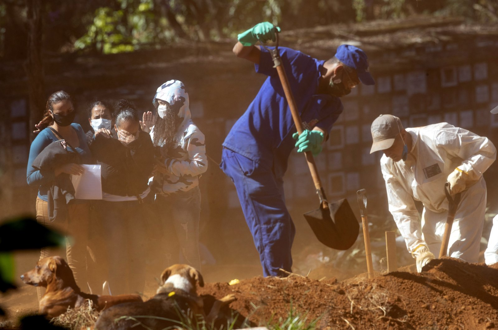 Relatives mourn as they watch cemetery workers shovel dirt over a coffin, at the Vila Formosa cemetery in Sao Paulo, Brazil, Thursday, May 28, 2020. (AP Photo/Andre Penner)