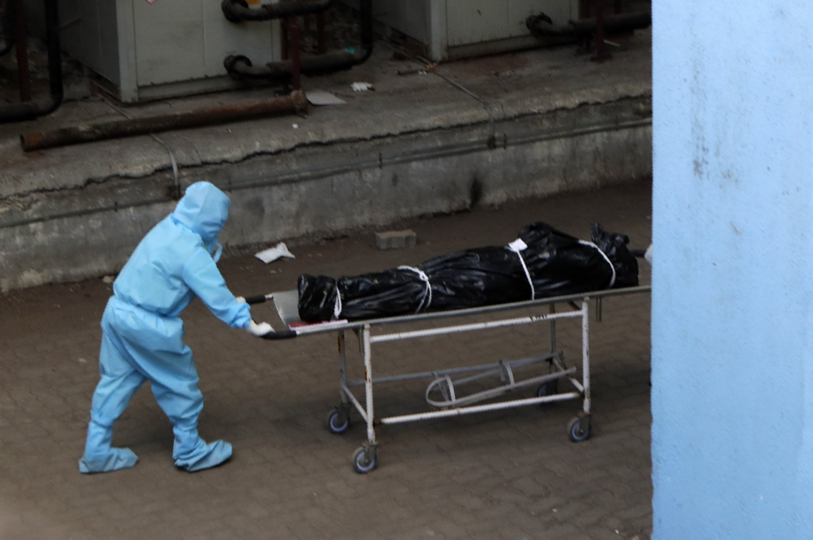 Hospital staff carries the body of a person who died of COVID-19 to a morgue in Mumbai, India, May 29, 2020. (AP Photo)