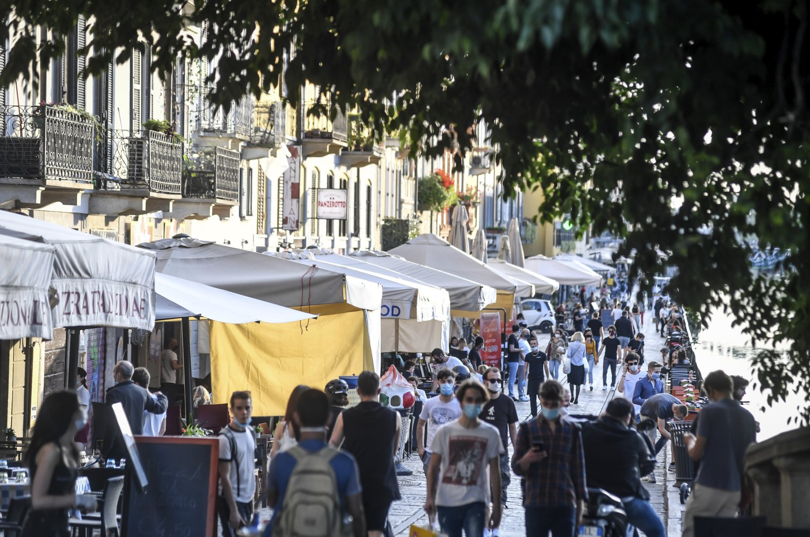 People walk in the city's trendy Navigli district in Milan, Italy, May 26, 2020. (AP Photo)