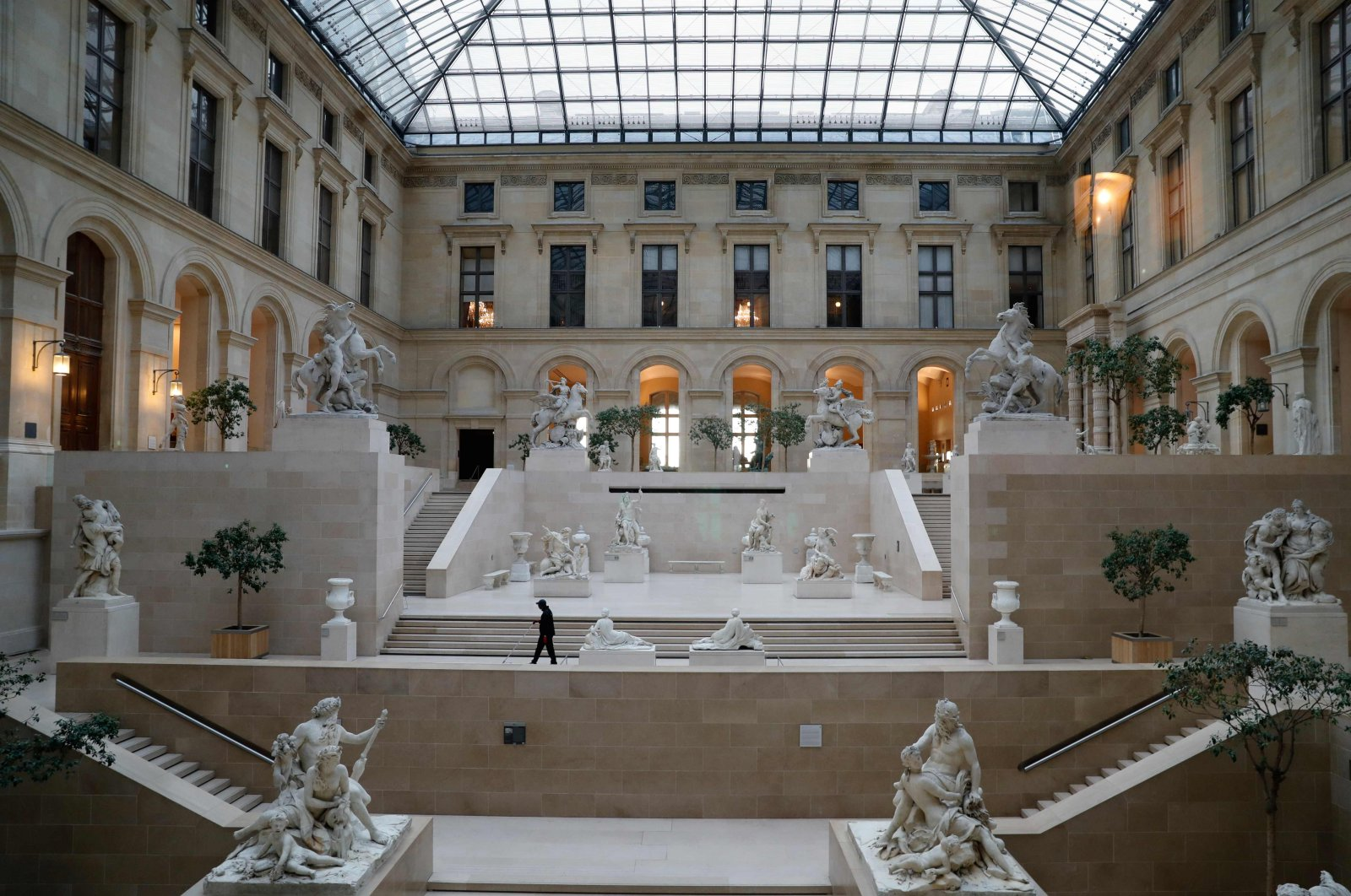 An employee walks in the Cour Marly at the Musee du Louvre in Paris, which was closed to the public since March amid concerns over the COVID-19 outbreak, Paris, France, March 13, 2020. (AFP Photo)