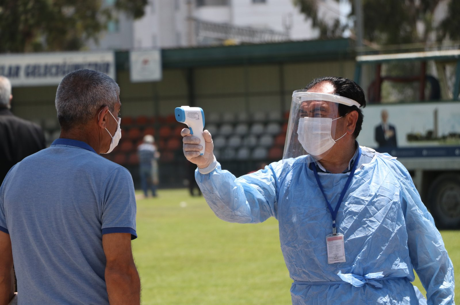 An official measures temperature of a citizen before Friday prayer in a stadium, Mersin, on May 29, 2020. (IHA Photo)