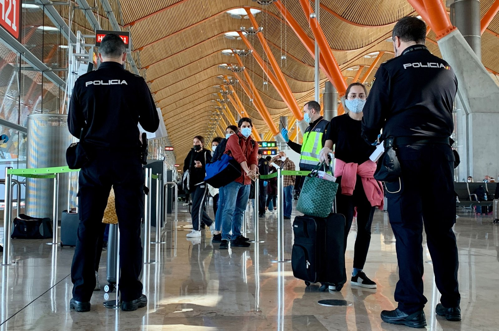 In this file photo taken on May 16, 2020 Spanish police officers check on passengers upon their arrival from Paris at the Madrid-Barajas Adolfo Suarez airport in Barajas. (AFP Photo)
