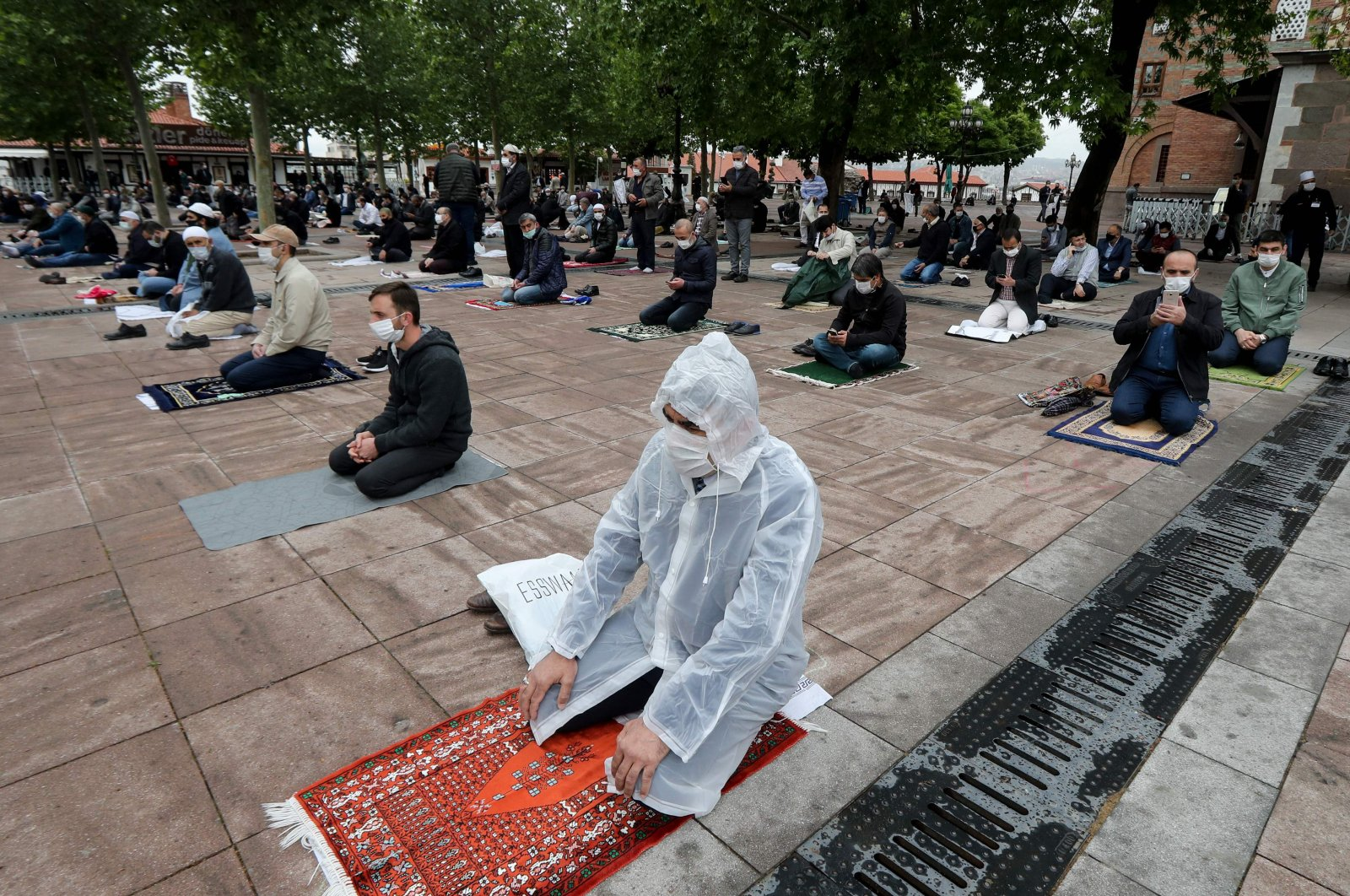 Worshippers wearing protective face masks maintain a required social distance during the Friday prayer outside the historical Hacı Bayram Mosque, in Ankara, Turkey, May 29, 2020. (AFP Photo)