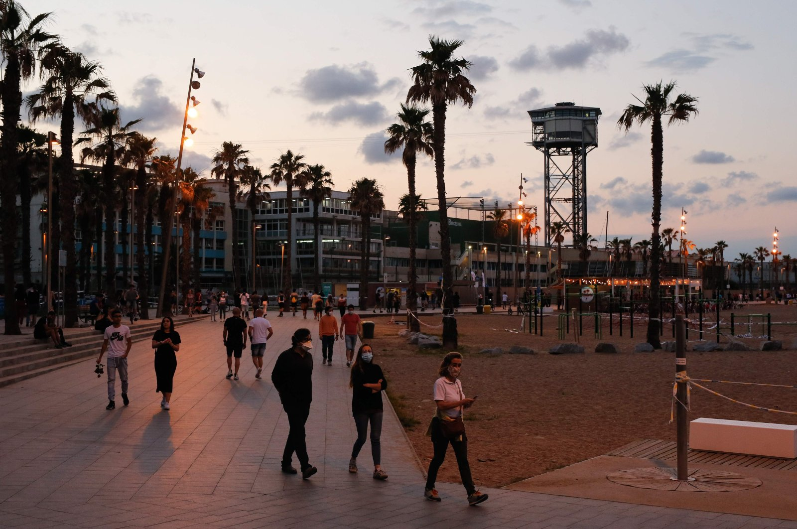People stroll along Barceloneta Beach in Barcelona on May 30, 2020 amid a national lockdown to prevent the spread of the novel coronavirus. (AFP Photo)