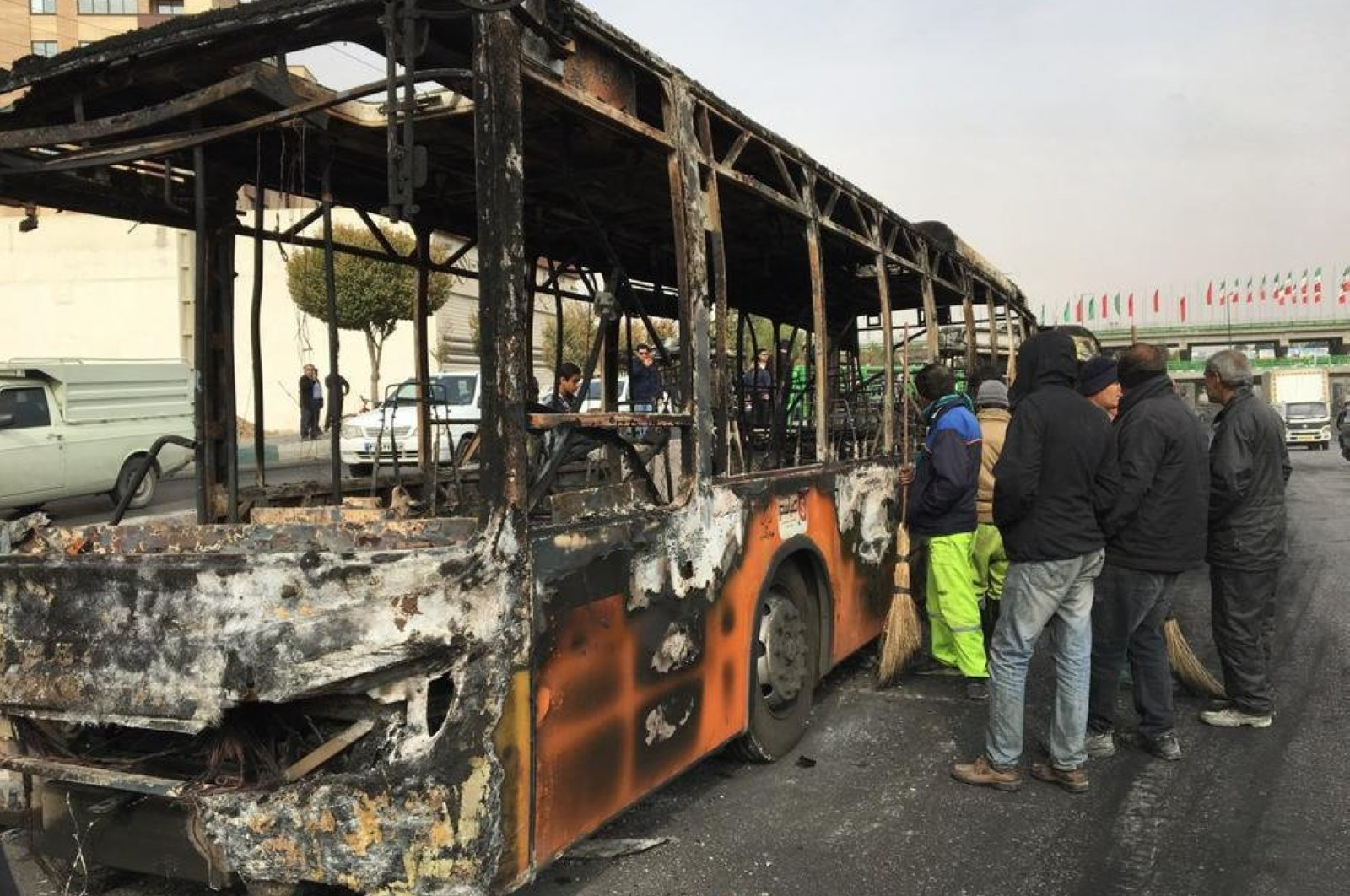 People gather around the wreckage of a public transportation bus that was burnt overnight during the protests over increasing fuel prices, Isfahan, central Iran, Nov. 17, 2019. (EPA-EFE Photo)