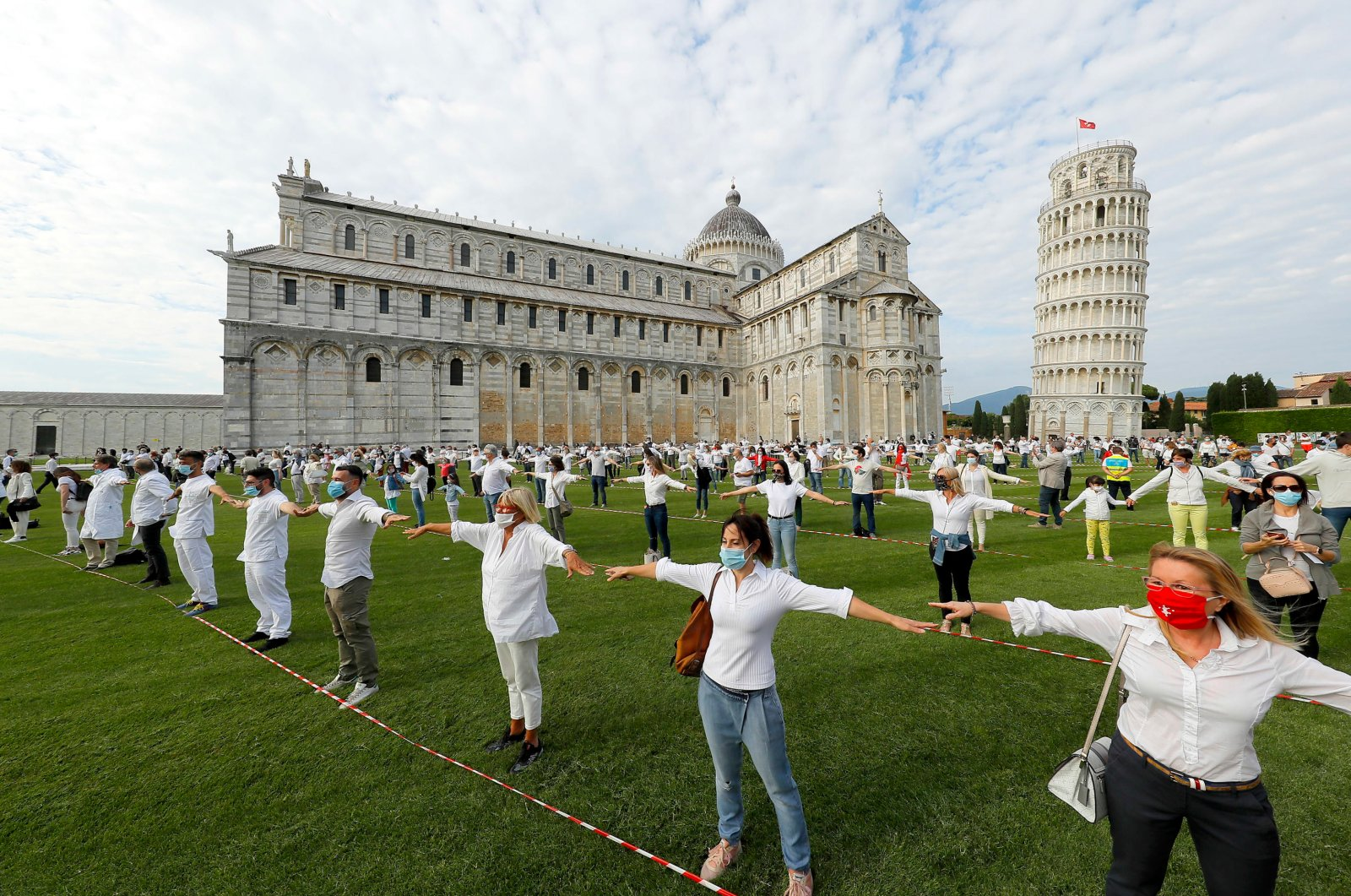 People gather for a flash mob on the Square of Miracles to celebrate the reopening of the Leaning Tower after it closed to contain the spread of COVID-19, In Pisa, Italy, May 30, 2020. (EPA Photo)