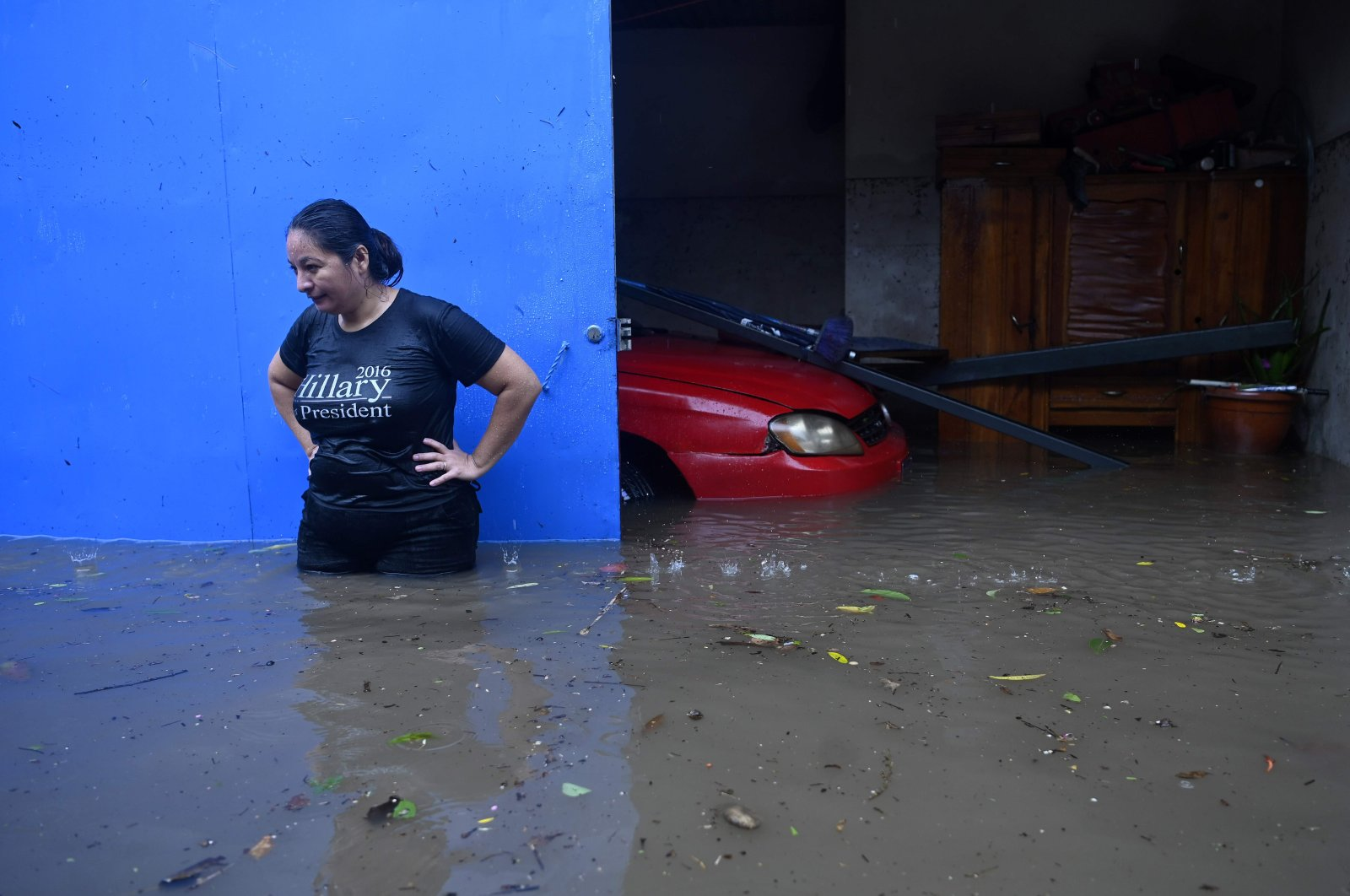 A woman is seen with floodwaters up to her hips as she stands outside her house in the flooded Santa Lucia colony in Ilopango, El Salvador, during Tropical Storm Amanda, May 31, 2020. (AFP Photo)