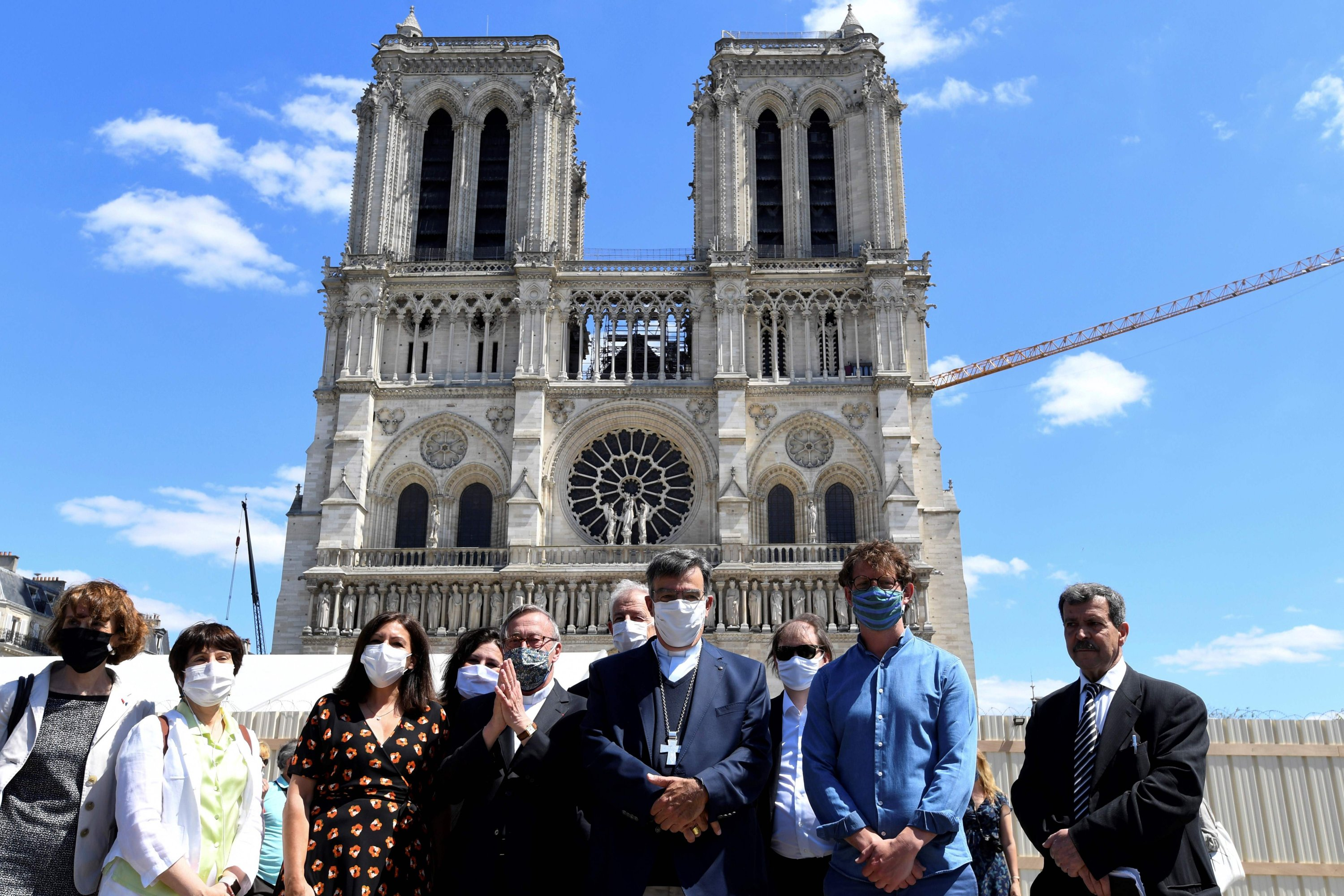 Paris Mayor Anne Hidalgo (3rd L) flanked by Notre Dame Cathedral rector Patrick Chauvet (5th L) and Paris Archbishop Michel Aupetit (C) pose in front of Notre Dame Cathedral on the first day of the cathedral's forecourt reopening, May 31, 2020. (AFP Photo)