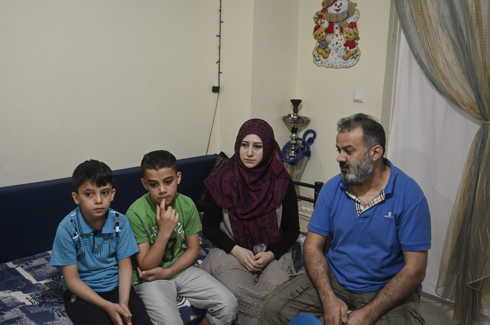 Abdelkader Rahmoun (R), a 44-year-old Syrian and his family sit in their apartment provided by NGO's through EU programs, at a working-class district in Piraeus near Athens on May 29, 2020. (AFP Photo)