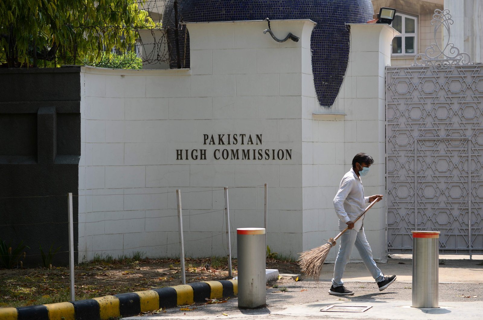 A man sweeps in front of the main gate of the Pakistan High Commission, New Delhi, June 1, 2020. (AFP Photo)